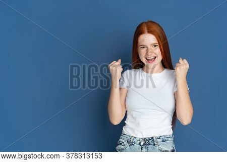 Winner, Celebrating. Caucasian Young Girls Portrait On Blue Background. Beautiful Female Redhair Mod