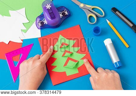 Child Makes Card With Christmas Tree. Original Children's Art Project. Diy Concept. Step-by-step Pho