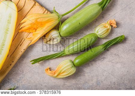 Zucchini And Zucchini Flower On Concrte  Background. Organic Food. Zucchini Vegetable Noodles