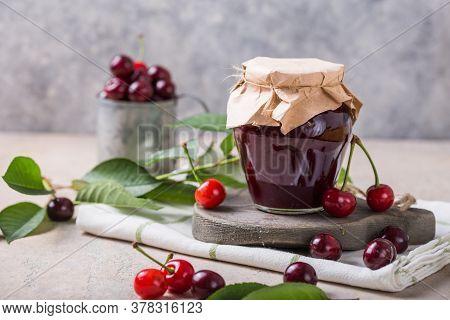 Cherry Jam. Jam In Glass Jar.  Homemade Sweet And Sour Cherry Jam With Fresh Cherries On Light Table