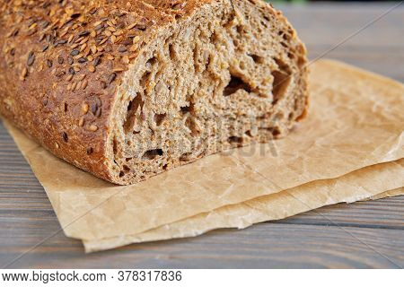Fresh Wholemeal Bread With Sunflower Seeds, Sesame And Others Grains On An Old Wooden Table.