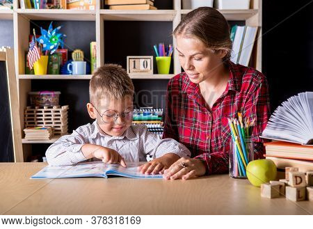 Female Primary School Teacher Helping A Young School Boy Sitting At Table In A Classroom, Close Up,