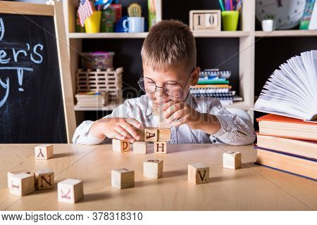 Kid Hands Playing Building Pyramid Of Cubes, Child Studying Construction In Classroom. Back To Schoo