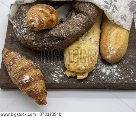 Several Types Of Bread Lie On A Rough Wooden Board On Light Background.