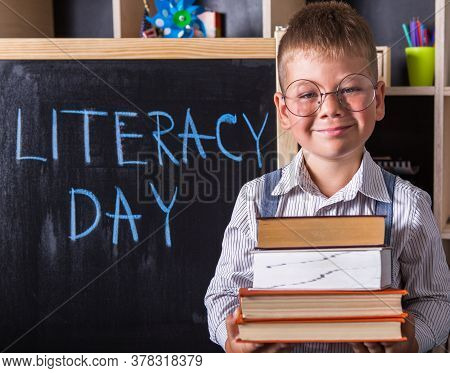 Portrait Of Cute Little Boy Holding Book In Classroom. Happy International Literacy Day. Back To Sch