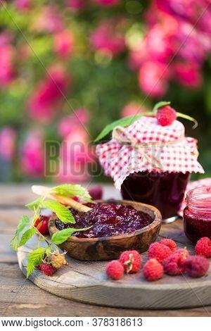 Fresh Raspberries Jam With Fresh Raspberries On Natural Garden. Selective Focus. Homemade Cherry Jam