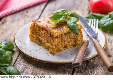 Meat Lasagna With Fresh Basil And Parmesan Cheese In A Plate On Wooden Table. Close Up. Italian Food