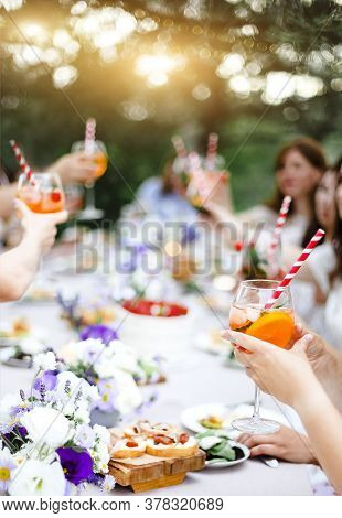 Unrecognizable People With Glasses Of Fruit Alcohol Drinks Proposing Toast While Sitting At Table Du