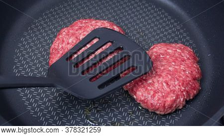 A Chef Puts Beef Patties On The Grill. A Juicy Beef Cutlet, Fried In A Pan. Close-up Of Beef Cutlet
