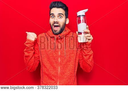 Young handsome man with beard wearing sportswear drinking bottle of water pointing thumb up to the side smiling happy with open mouth