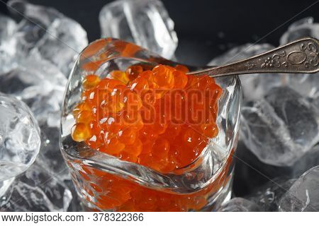 Red Caviar In Bowl On Ice Background. Close-up Salmon Caviar. Delicatessen