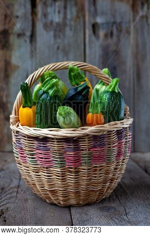 Set Of Multi-colored Zucchini In A Basket. Vegetable Squash On A Wooden Background. A Table With A H