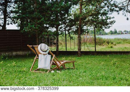 Wooden Deck Chair Under The Tree. Summer Holidays