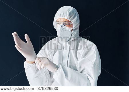 Doctor In Protective Medical Suit Puts On Protective Surgical Sterile Gloves On His Arm Isolated On