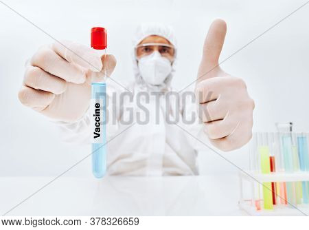 Scientist In Ppe Holding Vaccine Against Infection Disease And Showing Thumb Up. Virus, Immunization