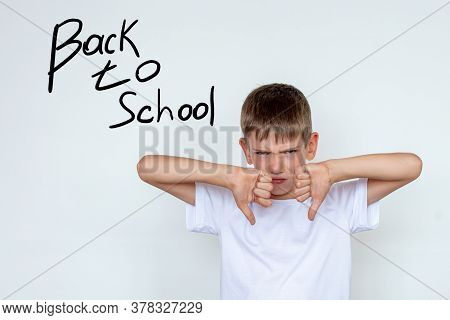 Portrait Of Unhappy, Unhappy Boy Making Thumbs Down Hand Gesture. The Boy Does Not Want To Study, Do