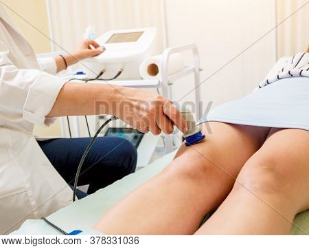 Doctor Using Machine To Treat The Knee Joints Of A Patient. T-care Technology.