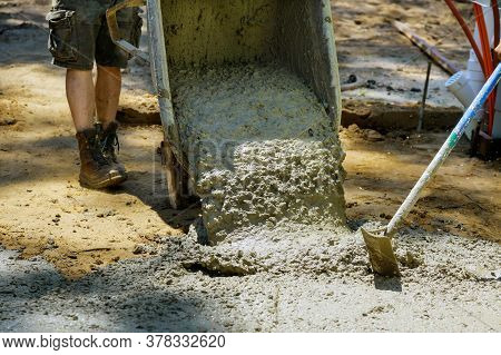 Construction Filling Formwork With Cement Worker Pour Cement For Sidewalk In Concrete With Wheelbarr