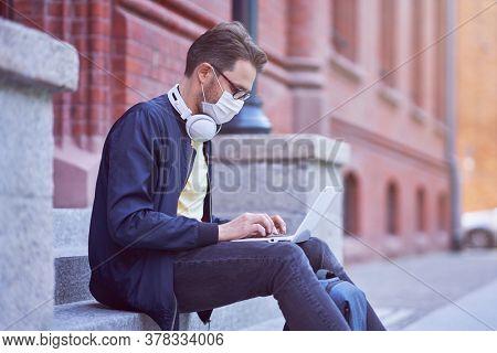 Male student in the campus wearing maskk due to coronavirus pandemic