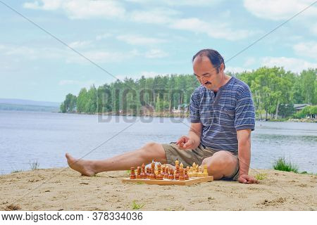 Senior Asian Man Pondering A Move In A Game Of Chess And Sitting On The Beach Near The Lake. Digital