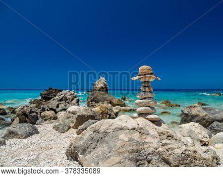 Straw Sunhat at the beach on balanced stones