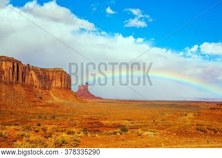 Magnificent rainbow across the sky. Huge masses of red sandstone - outliers on the Navajo Indian Reservation. The USA. Monument Valley is unique geological formation