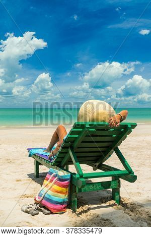 Woman on a sun lounger at the white sand Amazing tropical beach