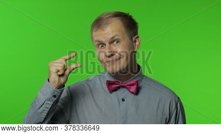 Positive Man Looking At Camera With Disappointed Pitiful Expression And Showing A Little Bit Gesture