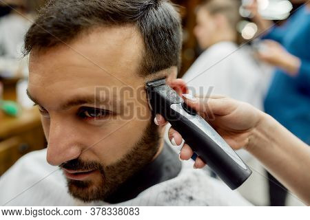 Close Up Shot Of A Young Handsome Bearded Man Getting Trendy Haircut While Visiting Barbershop. Barb