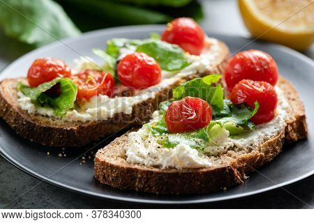Toast With Soft Ricotta Cheese, Roasted Tomatoes And Lettuce Garnished With Olive Oil And Black Pepp