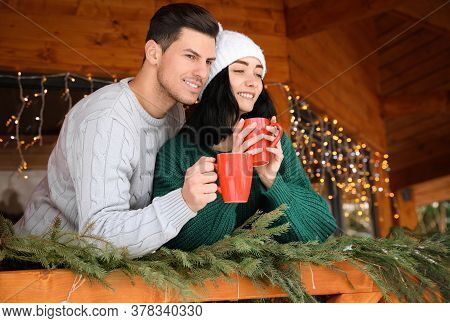 Happy Couple In Sweaters With Cups Near Decorated Railing