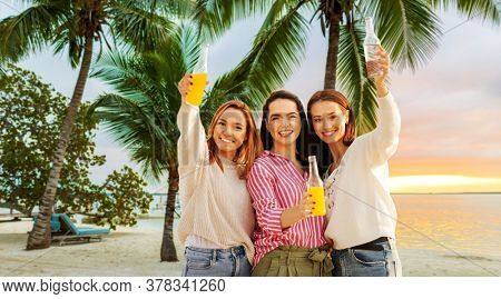 bachelorette party, friendship and travel concept - group of happy young women or female friends toasting non alcoholic drinks over tropical beach background in french polynesia
