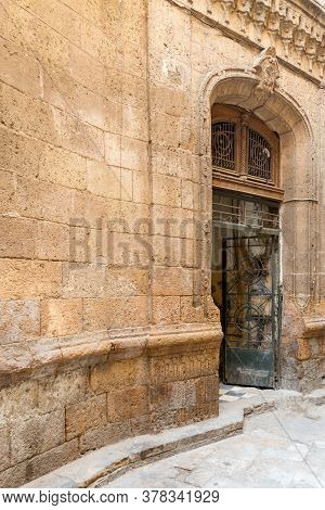 Angled View Of Grunge Door With Ferforge Wrought Iron Grill On Grunge Stone Bricks Wall In Abandoned