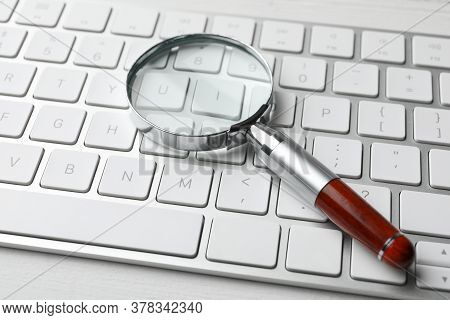 Magnifier Glass And Keyboard On White Table, Closeup. Find Keywords Concept