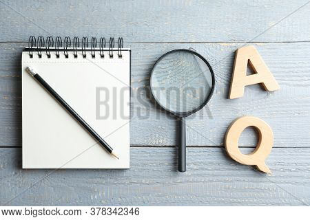 Flat Lay Composition With Notebook, Magnifier Glass And Letters On Light Grey Wooden Table. Find Key