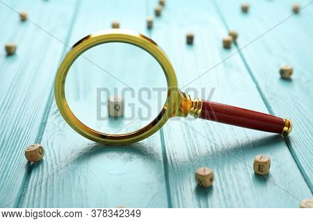 Magnifier Glass And Cube With Letter Q On Light Blue Wooden Background, Closeup. Find Keywords Conce