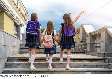 Schoolkids In School Uniforms Go Up The Stairs To School Against The Blue Sky. Hands Are Raised Up.