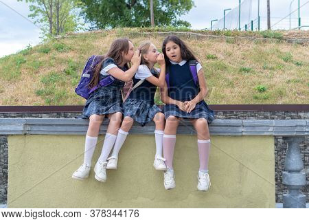 Three Schoolgirls Are Sitting In The Schoolyard. The Problem Of Adaptation And Communication At Scho