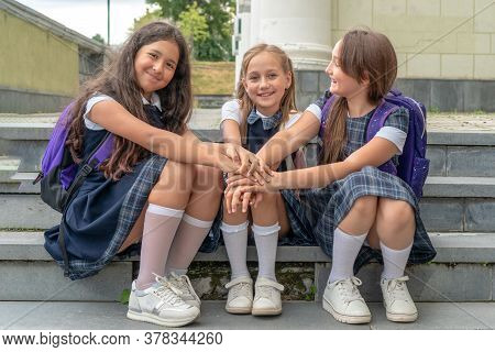 Schoolkids In School Uniform Are Sitting On The Stairs And Holding Hands. The Concept Of School Frie