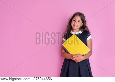 A Charming Girl With Long Curly Dark Hair In A School Uniform With A Book In Her Hands On A Pink Bac