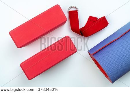 Accessories For Yoga And Pilates On A White Background: Support Bricks And A Belt For Proper Stretch