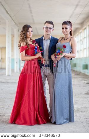 Handsome Guy In Blue Suit With Two Beautiful Girls In Glamorous Dresses. Ready For Their Prom Night