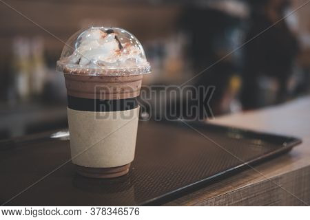 Closeup Of Takeaway Plastic Cup Of Iced Cocoa With Whipped Cream On Top.