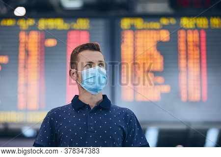 Man Wearing Face Mask Against Airport Departure Board. Themes New Normal, Coronavirus And Personal P