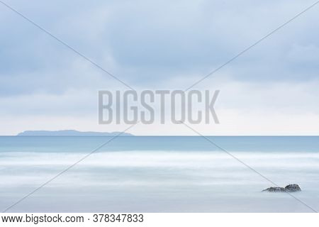 Tranquil Scene Of A Beach At The Sea With An Island In The Background And  A Rock In The Foreground