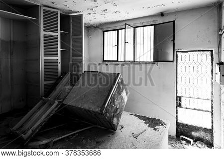 Interior Of An Old Abandoned House Kitchen With Damaged Wooden Furniture. Monocrome Photograph