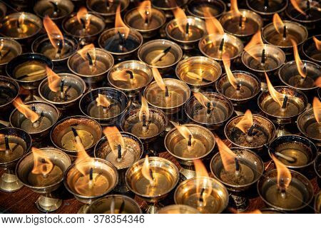 Group Of Oil Religious Candles Glowing With Orange Flames On A Hindu Temple. Symbols Of Faith And Re