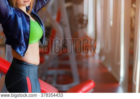 Fat Woman, Obese Woman Hand Holding Excessive Belly Fat Isolated On Gym Background, Overweight Fatty