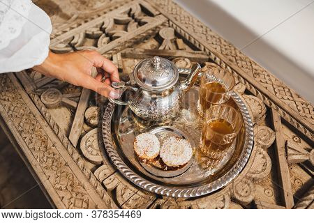 Woman Hands Serving Traditional Moroccan Mint Tea Ceremony With Cookies And Vintage Silver Teapot. H