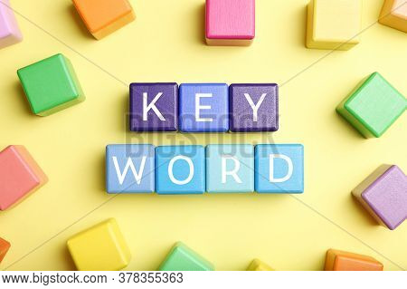 Colorful Cubes With Word Keyword On Yellow Background, Flat Lay